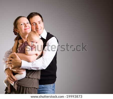 Studio picture of happy young parents and 4 months old baby girl over dark gray background - stock photo