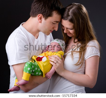 Studio picture of happy young parents and newborn girl over dark gray background - stock photo