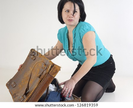 Studio picture of woman going to travel with suitcase