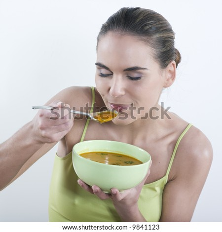 studio portrait isolated on white background of a beautiful caucasian woman eating soup - stock photo