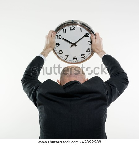 studio portrait isolated on white background of a man senior back holding a clock - stock photo