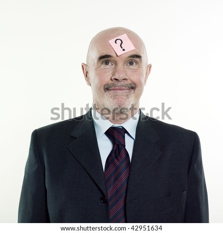 studio portrait isolated on white background of a man senior having a post-it with a question mark on his head - stock photo