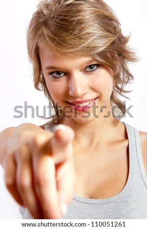 studio portrait of a beautiful blonde girl pointing to the camera
