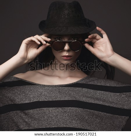 Studio portrait of a beautiful brunette girl in hat and glasses - stock photo