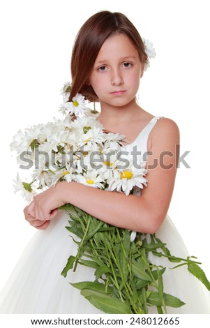 Studio portrait of a beautiful caucasian little girl in a white dress holding a lovely bouquet of white daisies - stock photo