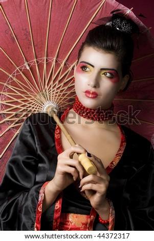 Studio portrait of a beautiful geisha - stock photo