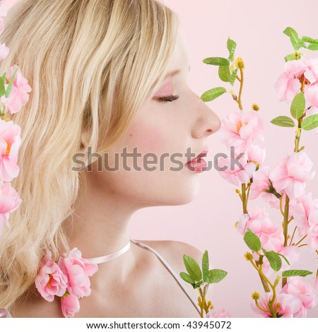 studio portrait of a beautiful girl with pink flowers