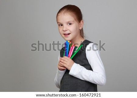 Studio portrait of a beautiful little schoolgirl with a sweet smile holding felt pens on a gray background