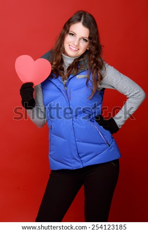 Studio portrait of a beautiful positive girl with romantic hair in warm clothing holding a red heart symbol of love on Valentine's Day - stock photo