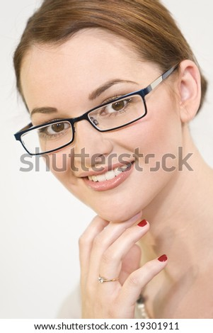 Studio portrait of a beautiful smiling young brunette woman with striking brown eyes and wearing glasses