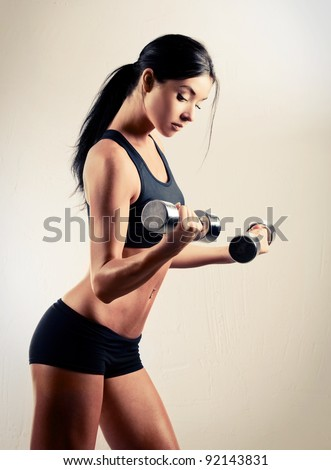 studio portrait of a beautiful sporty muscular woman working out with two dumbbells - stock photo