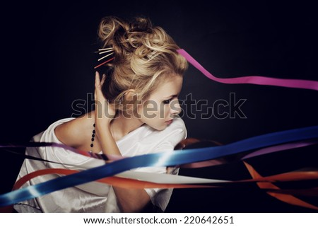 Studio portrait of a beautiful young blonde woman on a black background - stock photo