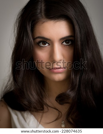 stock photo studio portrait of a beautiful young brunette woman with long hair looking straight into the camera 228074635