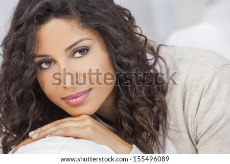 Studio portrait of a beautiful young mixed race Latina Hispanic woman smiling  - stock photo