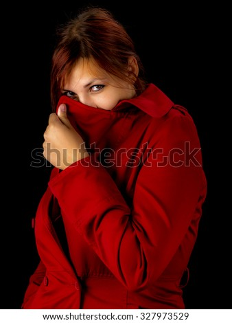 Studio portrait of a beautiful young woman in red coat, black background