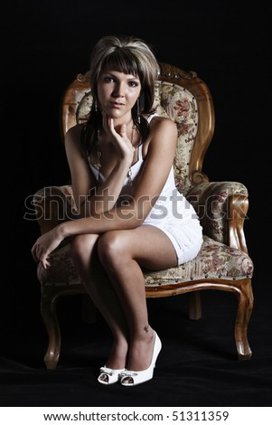 Studio portrait of a beautiful young woman sitting on a chair, isolated on a black background. - stock photo
