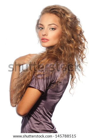 Studio portrait of a beautiful young woman with natural makeup, perfect skin and gorgeous curly hair