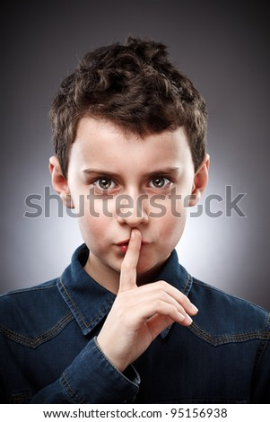 Studio portrait of a boy making silence sign - stock photo