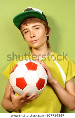Studio portrait of a boy teenager with football over green background.