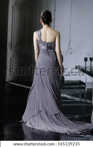 Studio portrait of a bride posing in a luxurious wedding dress -back full body in studio - stock photo