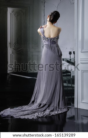 Studio portrait of a bride posing in a luxurious wedding dress -back full body in studio