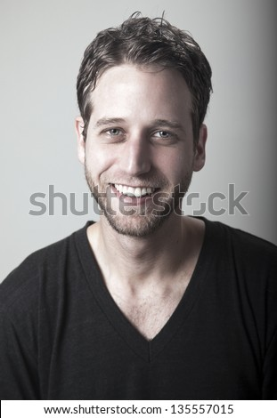 Studio portrait of a caucasian adult man in his early 30's over gray background. He seems to be in a good mood, looking at the camera with a large toothy smile on his face