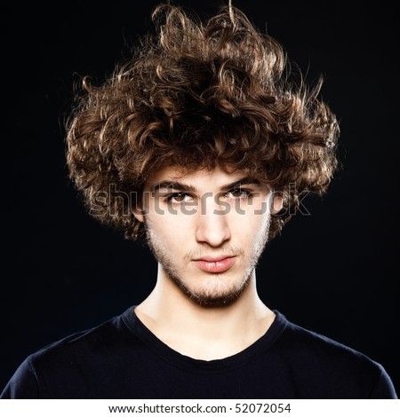 studio portrait of a cool young man on black background - stock photo