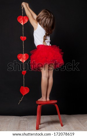 studio portrait of a cute little girl with a  heart in her hands - stock photo