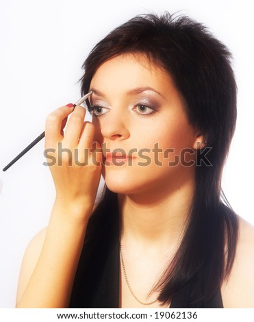 Studio portrait of a girl during makeup isolated on white background