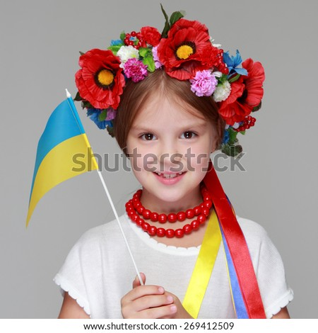 Studio portrait of a girl in the Ukrainian national costume holding a flag of Ukraine on a gray background - stock photo