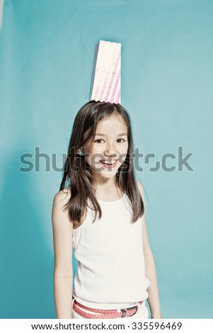 Studio portrait of a girl with a popcorn container on her head - stock photo