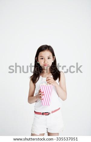 Studio portrait of a girl with popcorn - stock photo