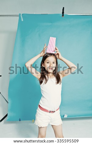 Studio portrait of a girl with popcorn container on her head - stock photo