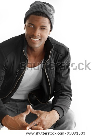 Studio portrait of a good looking happy young black man in trendy clothes against white background with copy space