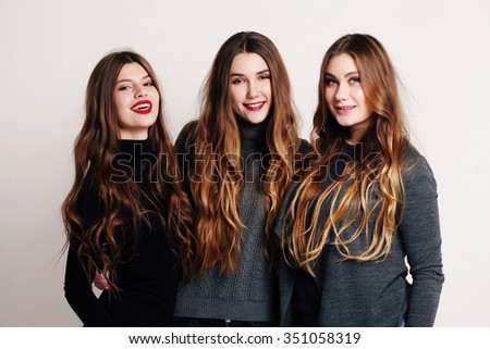 Studio portrait of a group of three young beautiful model smiling and having fun. Consumer concept, winter fashion, attractive young women