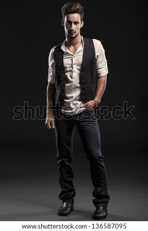Studio portrait of a handsome and fashion young man, posing over a dark background - stock photo