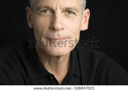 Studio Portrait of a handsome man with grey hair looking to the camera - stock photo
