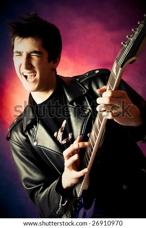 studio portrait of a happy excited young man playing guitar and screaming - stock photo