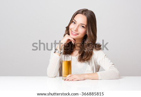 Studio portrait of a happy young brunette woman with glass of apple juice. - stock photo