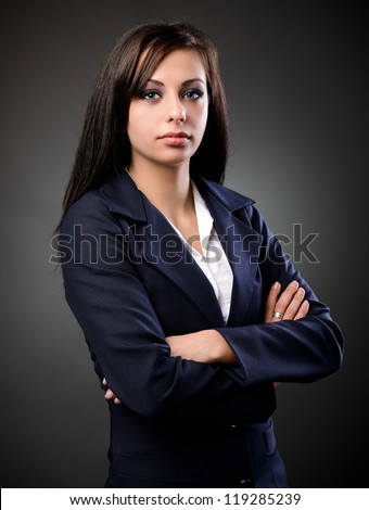 Studio portrait of a latin businesswoman in suit, against dark background - stock photo