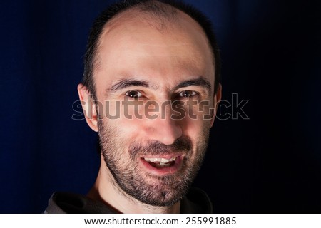 Studio portrait of a laughing middle aged unshaven man - stock photo