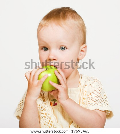 Studio portrait of a little girl eating an apple - stock photo