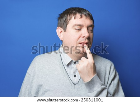 studio portrait  of a man biting nails anxious nervous - stock photo