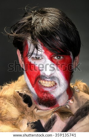 studio portrait of a man in war paint on a dark background, furiously rock, the barbarian of ancient times, Viking and savage.