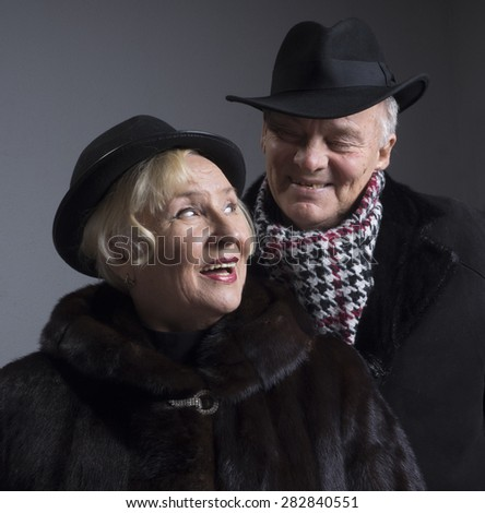 Studio portrait of a middle-aged couples, dressed in a fur coat - stock photo