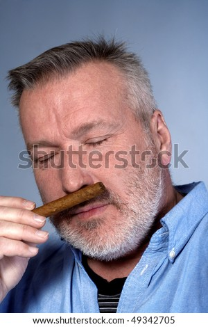studio portrait of a middle aged man in shirt with a cigar - stock photo