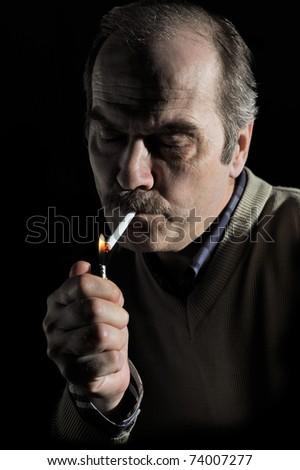 Studio portrait of a mustached man lighting cigarette over black - stock photo