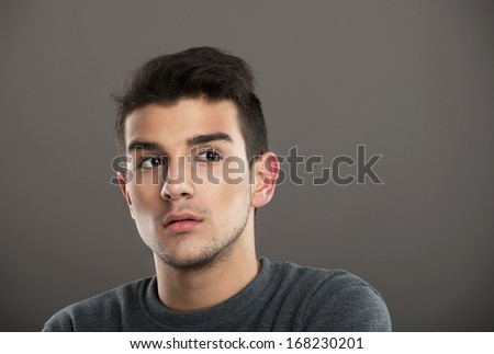 Studio portrait of a pensive youth on gray background - stock photo