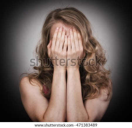 Studio portrait of a sad girl covering her face with the hands