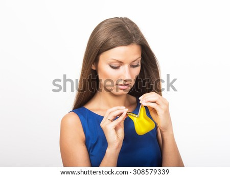 Studio portrait of a sad girl looking into her empty purse - stock photo